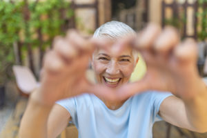 Positivity. Happy Funny Senior Woman Showing Symbol of Heart. Cute senior old woman making a heart shape with her hands and fingers. Perfect, nice, aged, old, pretty woman